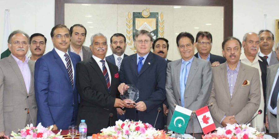 ISLAMABAD, JUL 18: President ICCI, Khalid Iqbal Malik presenting a souvenir to Perry John Calderwood, High Commissioner of Canada at Chamber House.=DNA PHOTO