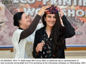 ISLAMABAD, NOV 13: Batik expert Ms Fonna offers a traditional cap to representative of Iqra University during Batik Eco Print workshop at the Indonesian embassy on Wednesday. DNA