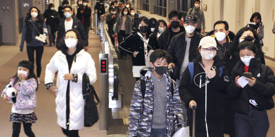 Passengers wearing face masks arrive at Narita airport in Narita, near Tokyo Saturday, Jan. 25, 2020. Hong Kong has declared the outbreak of a new virus an emergency and will close primary and secondary schools for two more weeks after the Lunar New Year holiday. City leader Carrie Lam also announced Saturday that trains and flights from the city of Wuhan would be blocked. (Kyodo News via AP)