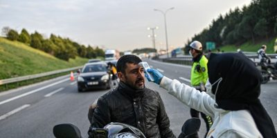 "A Turkish health official checks the temperature of a motorcyclist at a check point, on the Asian side ,entry of Istanbul on March 30, 2020. - President Recep Tayyip Erdogan called on Turks to stay at home and adapt themselves to "" voluntary quarantine "" conditions. (Photo by Ozan KOSE / AFP)"